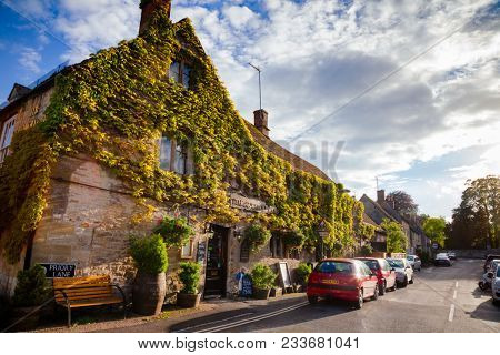 BURFORD, UK - JUN 13, 2013: The Cotswold Arms, a taditional inn with floral decor and a garden terrace, serving real ale and home-cooked pub food