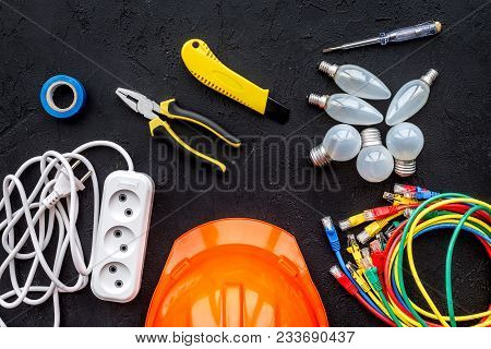 Electrician Work Concept. Hard Hat, Tools, Cabel, Bulb, Socket Outlet On Black Background Top View.