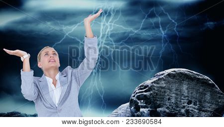 Digital composite of Businesswoman with arms raised by rock against thunderstorm