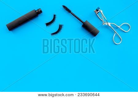 Cosmetics And Tools For Voluminous Lashes. Mascara, False Eyelashes, Eyelash Curler On Blue Backgrou
