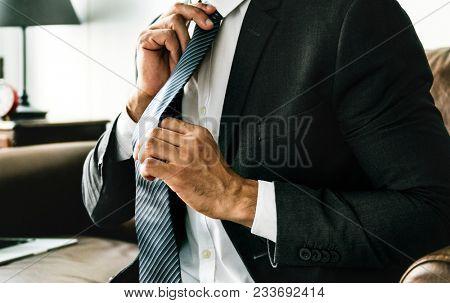 Businessman tying his necktie