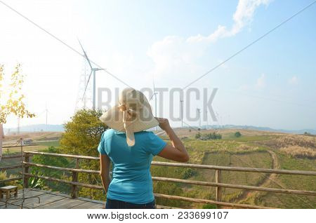 Asian Girl Looking At Windmills On Mountain In  Blue Sky Background  At Khao Kho In Petchabun Provin