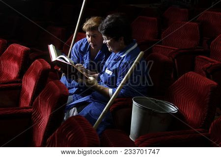Encouraging people to read.Book reading.Cleaners in the theater reading a book poster