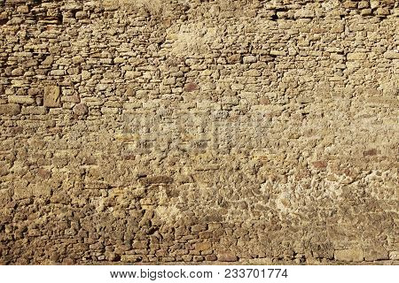 The Texture Of The Ancient Ancient Wall Of The Fortress Made Of Stone Illuminated By The Sun