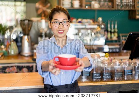 Happy Attractive Asian Barista Offering To Taste Coffee In Cafe. Positive Young Woman In Eyeglasses