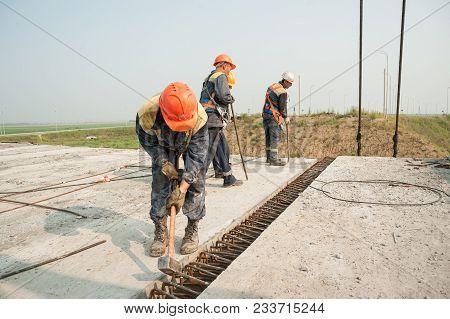 Tyumen, Russia - July 31, 2013: Jsc Mostostroy-11. Manual Workers Mount Span Of Bridge. Bridge Const