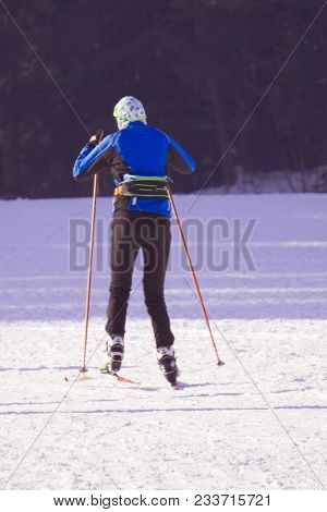Young Active Woman Skiing In Mountains. Female Skier Kid With Safety Helmet, Goggles And Poles Enjoy