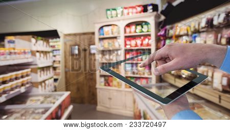 Digital composite of Hand taking picture with tablet PC at grocery store
