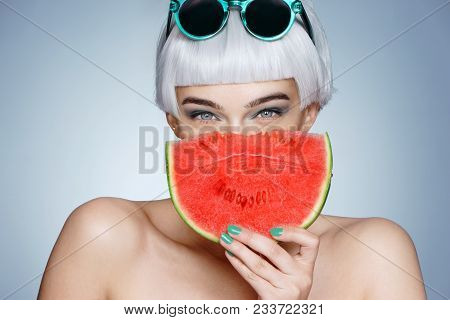 Summer Time. Pretty Young Girl Holding Slice Of Watermelon In Front Of Her Face On Blue Background.