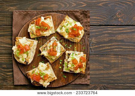 Omelet, Scrambled Eggs On Toasted Bread With Green Onion And Tomato Over Wooden Background With Copy