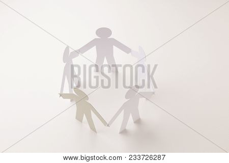 Closed Joining Of Five Paper Figure With Gray One In Hand Down Posture On Bright White Background. I