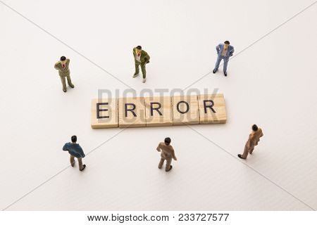 Miniature Figures Businessman : Meeting On Error Letters By Wooden Block Word On White Paper Backgro