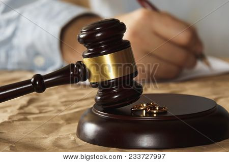 Male Hand Pushing A Wedding Ring Over To A Female Hand About To Sign Divorce Papers. Conceptual Of D