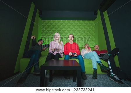 A Group Of Friends Sitting On The Couch And Playing Games On The Console. Many Young People On The C