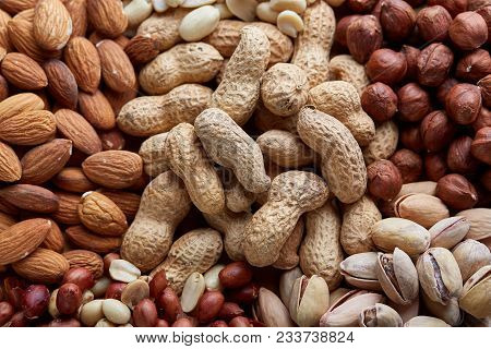 Assorted Tasty Nuts Background, Top View, Close-up, Selective Focus. Peanut, Hazelnut, Pistachio, Al