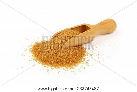 Close up one wooden scoop spoon full of raw brown cane sugar with pinch spilled and spread around, isolated on white background, low angle view poster