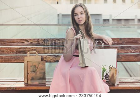 Attractive Serious Woman After Shopping, Sitting On A Bench, Resting And Parses Purchases. Look At T