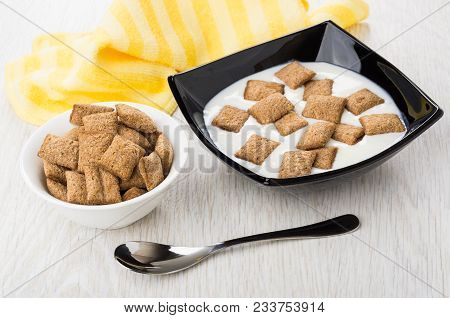 Black Bowl With Yogurt And Cereal Pillows, Bowl With Pillows, Yellow Napkin, Spoon On Wooden Table