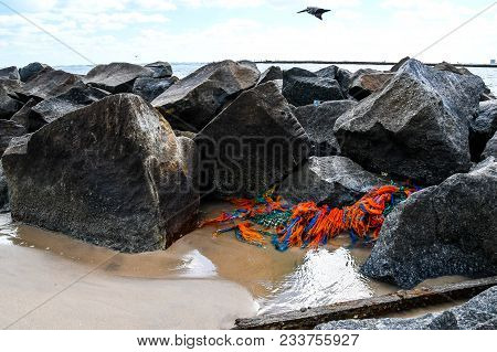 Colorful Debris Of Netting And Ropes Deposited By Tidal Waves On A Rock Jetty On A Florida Beach As