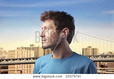 Profile of a young man listening to music with cityscape in the background