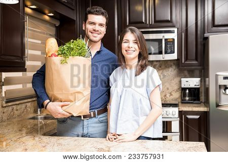 Portrait Of Happy Young Hispanic Couple Holding Paper Bag With Fresh Vegetable And Grocery In Kitche