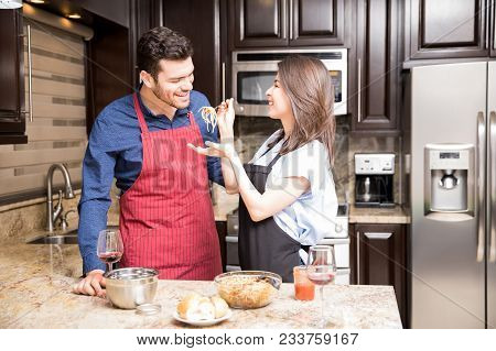 Handsome Young Man Tasting Food Prepared By His Girlfriend In Kitchen At Home