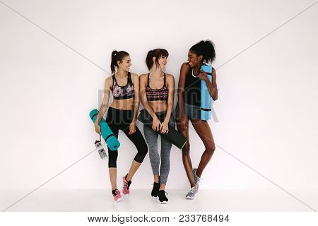 Group Of Female Friends In Sportswear Smiling Together While Standing In A Gym After Yoga Workout. W