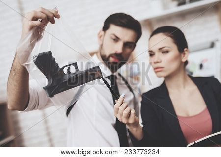 Private Detective Agency. Man With Holster And Woman Are Looking At Gun Clue And Taking Notes.