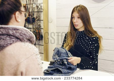 Female Shop Assistant Talking With The Customer, In The Checkout Of A Clothing Store. Something Is W