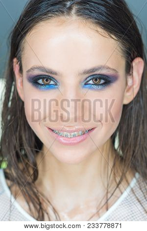 Woman With Braces On Teeth. Happy Girl Smile With Dental Braces. Woman Smiling With Bright Eye Makeu