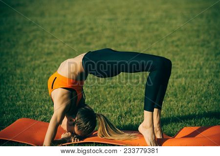 Bodycare woman in crab position on green grass, body care. Bodycare, fitness, wellness, health. poster