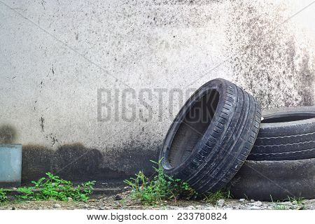 Pile Of Old Worn And Dirty Car Tires With Weed On Wall Background In Garage.recycle And Business Con
