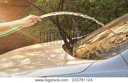 Female Hand Washing Car With Rubber Tube And Water Spray To The Mirror In Motion Blurred On Flare Fr