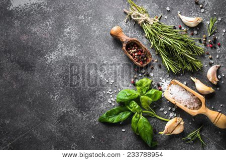 Spices And Herbs Over Black Stone Table. Food Background. Top View, Copy Space.