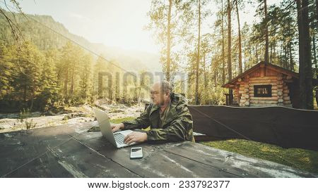 Adult Partly Bald Hunter Is Sitting Outdoors Near His Shack At The Wooden Table And Working On His L