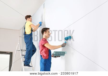 Young professional male decorators refurbishing empty room poster