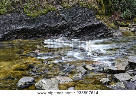 A Shallow Rocky Creek Landscape With Smooth Whitewater.