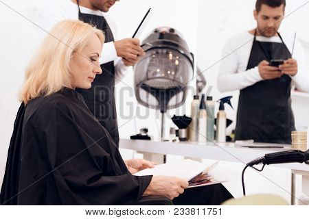 Mature Attractive Woman On Pair With Hairdresser Choose Style For Future Haircuts In Beauty Salon. M