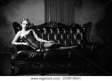 Sensual Young Girl Dressed In A Corset, Stockings And Panties Lying On Sofa. Black And White Portrai