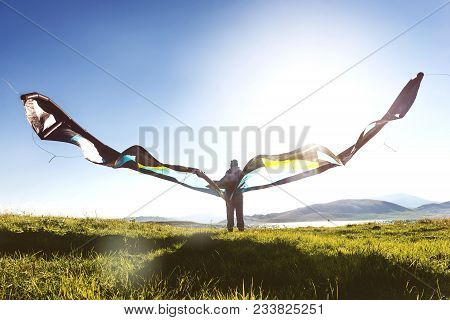 Man Or Woman Stands With Kite Against Blue Sky And Sun Light
