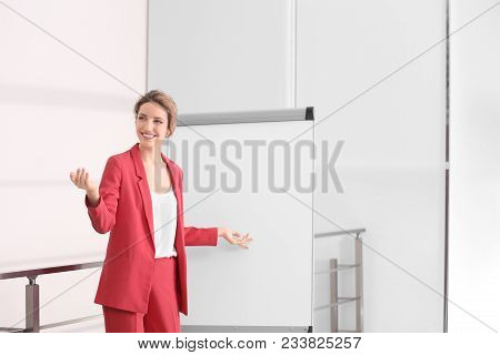 Female Business Trainer Giving Presentation On Whiteboard Indoors