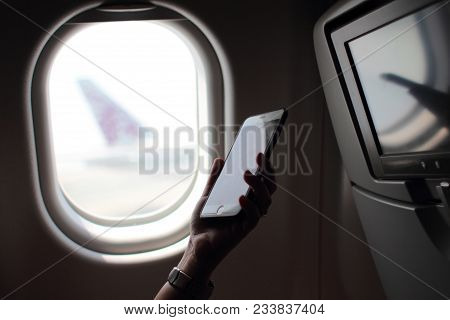 Woman Hands Using Smart Phone On The Plane Using The Internet. Near The Window When The Plane Is Par