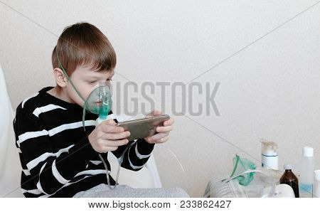 Use Nebulizer And Inhaler For The Treatment. Boy Inhaling Through Inhaler Mask And Playing The Game