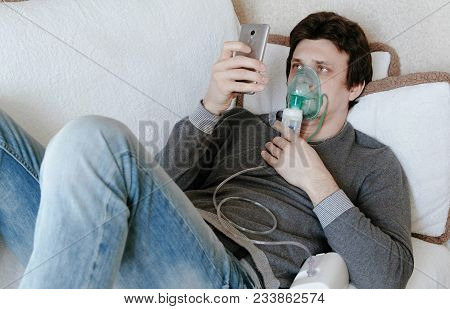 Use Nebulizer And Inhaler For The Treatment. Young Man Inhaling Through Inhaler Mask Lying On The Co