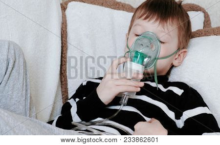 Using Nebulizer And Inhaler For The Treatment. Boy With Cloused Eyes Inhaling Through Inhaler Mask L