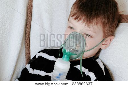 Using Nebulizer And Inhaler For The Treatment. Boy's Face Inhaling Through Inhaler Mask Lying On The