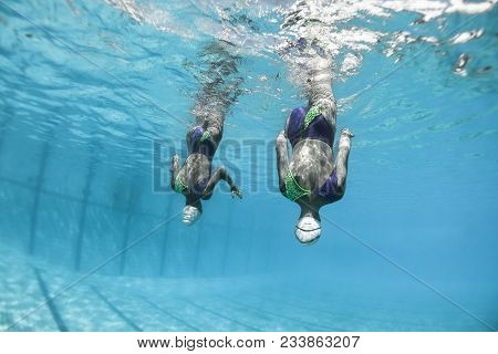 Aquatic Swimmers Doing Synchronized Swimming Dance Moves , Closeup Underwater Action Photo Of Uniden