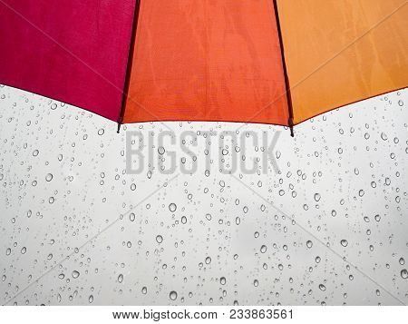 Red Orange Yellow Umbrella With Rain Water Drop In Background.