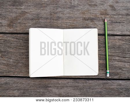 Opened White Page Of Blank Notepad Notebook And Green Pencil On Wood Texture Background.