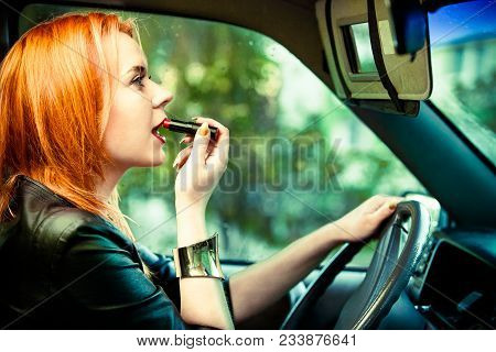 Concept Of Danger Driving. Young Woman Driver Red Haired Teenage Girl Painting Her Lips Doing Make U